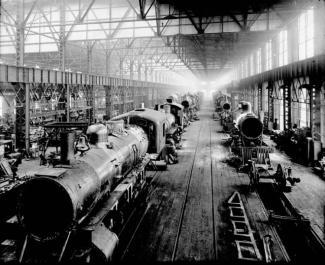 Vue sur des locomotives dans une grande salle de montage lumineuse..