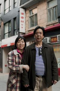 Photo couleur d'une femme et d'un homme se tenant debout collés l'un contre l'autre devant un édifice dans le quartier chinois.