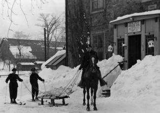 Photographie en noir et blanc sur laquelle on voit un policier à cheval tirant une civière attelée à l'animal. Derrière la civière, il y a deux policiers à ski.