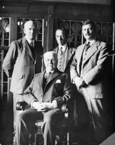 Photo en noir et blanc de quatre hommes en complet, trois sont debout et un est assis devant.