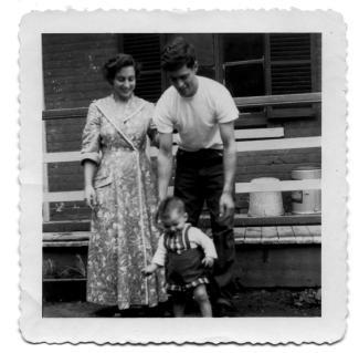 Photographie de deux parents souriant derrière leur jeune enfant.