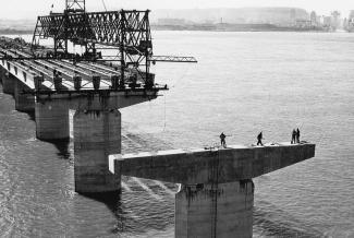 Construction d'un pont au milieu d'un cours d'eau, avec la ville en arrière-plan. En avant-plan, on aperçoit quatre hommes sur une des piles qui n'est pas encore reliée aux autres sections.