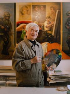 Photo couleur d'un artiste tenant un pinceau et une palette de couleurs dans son atelier