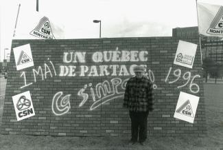 Un homme pose devant une murale où on peut lire le slogan « Un Québec de partage, ça s'impose. 1 mai 1996 ».