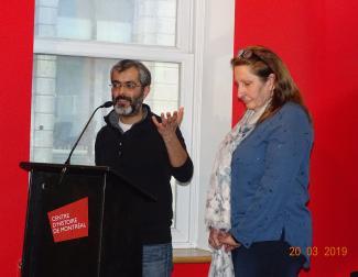 Un homme parle au micro et une femme se tient à ses côtés