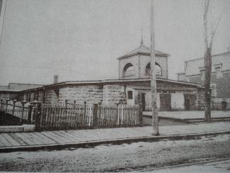 Photo ancienne d'un bâtiment coiffé d'un clocher de chapelle.