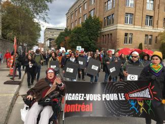 Des dizaines de personnes marchent dans la rue tenant des affiches. On peut lire sur certaines d'entre elles : « Engagez-vous pour le communautaire ».