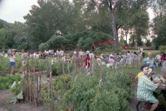 Plusieurs dizaines de personnes sont rassemblées à côté des parcelles d'un jardin. Certaines sont attablées à une table à pique-nique, d'autres sont assises sur des chaises pliantes.