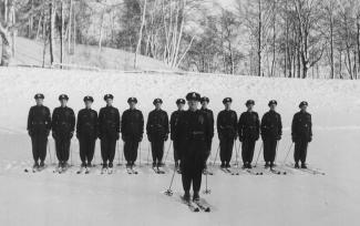 Photographie en noir et blanc sur laquelle on voit des policiers à ski se tenir en ligne droite. L'un d'eux se tient devant la ligne.