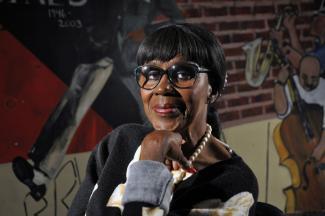 Photo en couleurs d'une femme noire portant des lunettes et prenant la pose.
