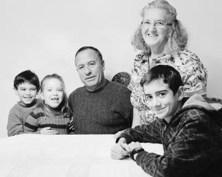 Photo en noir et blanc montrant un grand-père, assis, sa femme à ses côtés, debout, et leurs trois petits-enfants autour d'eux, deux d'un côté et un de l'autre.