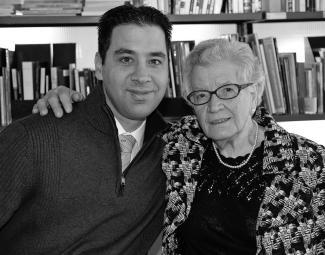Photo en noir et blanc d'une jeune homme et de sa grand-mère se tenant par les épaules, collés l'un contre l'autre. Une bibliothèque en arrière-plan.