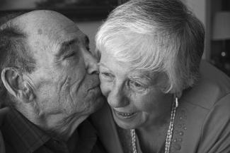 Photo en noir et blanc d'un homme âgé embrassant sa femme sur la joue en plan rapproché. .