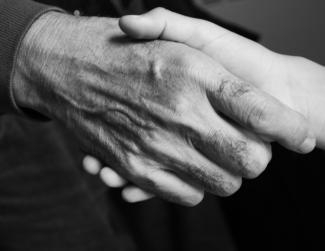 Photo en noir et blanc montrant deux mains qui se serrent en plan rapproché.