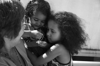 Photo en noir et blanc montrant une grand-mère et ses deux petites filles en plan rapproché.
