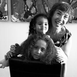 Photo en noir et blanc montrant une grand-mère et ses deux petites-filles, l'une derrière l'autre en plan rapproché.