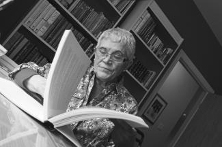 Photo en noir et blanc montrant une femme en plan rapproché tournant les pages d'un cahier.