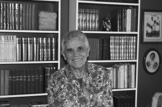 Photo en noir et blanc montrant une femme en plan rapproché avec des bibliothèques en arrière-plan.