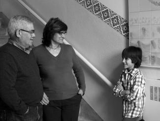 Photo en noir et blanc d'un jeune garçon, debout, regardant son grand-père et sa grand-mère, aussi debout. Ils sourient tous les trois.
