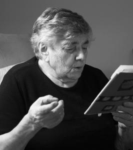 Photo en noir et blanc montrant une grand-mère et tenant un livre en plan rapproché.