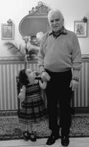 Photo en noir et blanc montrant une petite-fille, debout, qui lève les yeux vers son grand-père, debout à côté d'elle et lui tenant la main. .