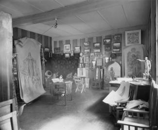Table de travail au premier plan, avec matériel artistique. Au deuxième plan, des vitraux et des  esquisses sont accrochées au mur.