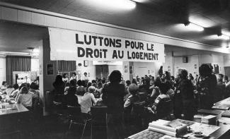 Une cinquantaine de personnes sont assises ou debout, de dos, dans une salle. Une affiche, sur laquelle on peut lire « Luttons pour le droit au logement », est suspendue au plafond.