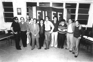 Groupe de neuf hommes posant debout devant des fenêtres d'un local et une banderole sur laquelle est écrit le mot FILEF.