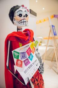 Squelette décoré tenant l'affiche de la Fête des Morts 2014