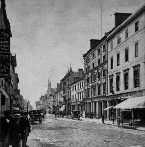 Photographie d'une rue avec de hautes façades et de calèches.