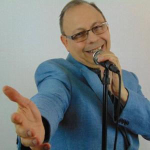 Plan rapproché d'un homme qui chante en tenant un micro.