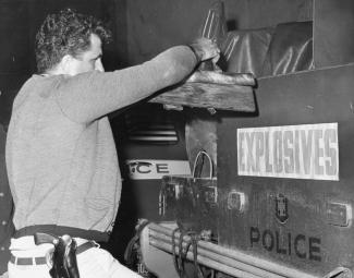 Un policier vu de côté est en train de prendre de l'équipement dans un camion sur lequel on peut lire « Explosives » et « Police ».