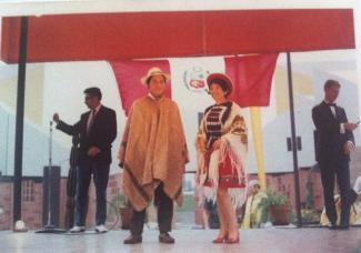 Un homme et une femme en habits traditionnels péruviens se tiennent sur une scène. En arrière-plan, deux hommes habillés d'un veston noir.