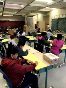 Onze élèves sont assis à leur bureau et travaillent avec du matériel de bricolage.