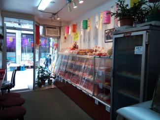 Photo couleur montrant l'intérieur d'une pâtisserie traditionnelle chinoise. On voit une rangée de comptoirs à droite et des bancs à gauche, et la porte vitrée donnant sur la rue De La Gauchetière au fond.