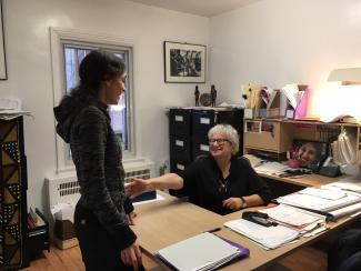 Deux femmes souriantes dans un bureau, l'une assise derrière le bureau, l'autre debout devant