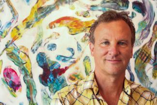 Gros plan sur un homme souriant avec une œuvre picturale derrière lui