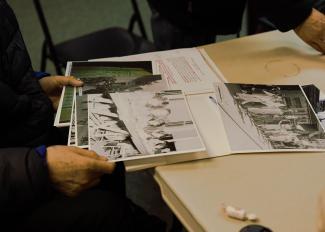 Gros plan sur les mains d'un homme montrant des photos anciennes dans un dossier.