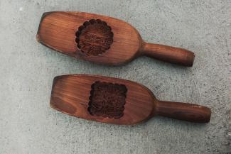 Deux moules en bois à gâteaux de lune avec des motifs dans la partie creuse et le nom de la pâtisserie en écriture chinoise.