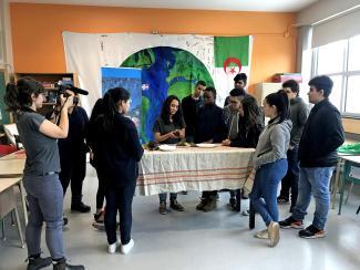Douze élèves rassemblés autour d'une table. Une vidéaste filme.