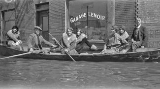 Cinq femmes et deux hommes sont dans une chaloupe dans une rue inondée devant un édifice de brique.
