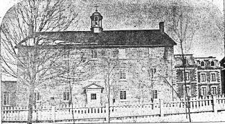Photographie en noir et blanc représentant un édifice de trois étages, au toit mansardé, avec un clocheton.