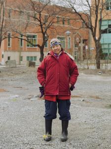 Photo couleur plein pied d'une femme portant des bottes de caoutchouc et une casquette dans un terrain vacant du Quartier chinois.