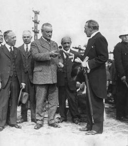 Photo en noir et blanc montrant un groupe d'hommes en costume. L'un présente un objet à un autre.