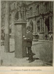 Photographie en noir et blanc tirée d'une coupure de journal. On y voit un policier en uniforme près d'une boîte d'alarme.