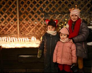 Trois enfants habillés chaudement avec une rangée de bougies allumées à leur gauche