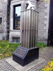 Photo d'une œuvre d'art public comportant une sculpture trônant sur un socle où sont écrits les noms de personnes incarcérées lors de la crise d'octobre 1970.