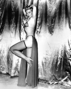 Une femme blonde se tient debout, de profil, les bras relevés derrière la tête et une jambe repliée. Elle porte un costume de scène deux pièces avec un long voile à l'arrière, allant de la taille jusqu'aux pieds.