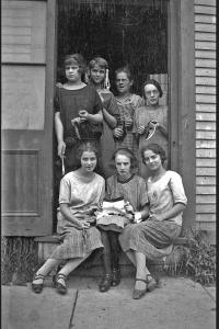 Sept femmes, dont trois assises et quatre debout derrière elles, dans l'entrée d'un édifice.