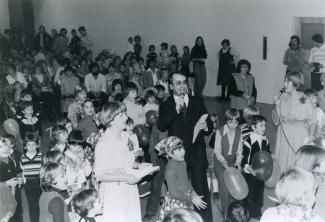 Un homme et une femme sont debout et tiennent chacun un microphone. Autour d'eux se trouve une foule composée d'enfants et de quelques adultes.
